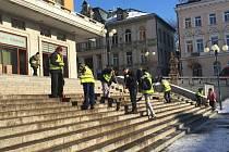 Pracovníci veřejně prospěšných prací uklízí schody před radnicí.