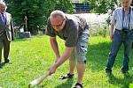 Archeolog Jan Prostředník seká kamenou sekyrkou.