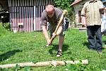 Archeolog Jan Prostředník seká kamenou sekyrkou. Přihlíží Vladimír Šrein.