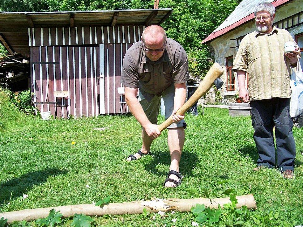 Archeolog Jan Prostředník seká kamenou sekyrkou.Přihlíží Vladimír Šrein.