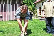 Archeolog Petr Šída seká kamenou sekyrkou.Přihlíží Vladimír Šrein.