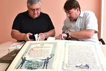 Pavel Pilz ze Státního okresního archivu Jablonec nad Nisou (vlevo) a starosta Janova nad Nisou Daniel David nahlížejí do archiválií týkajících se historie dobrovolných hasičů v Janově