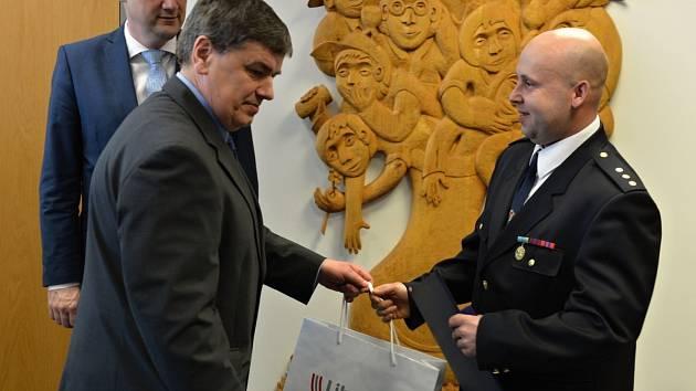 Petr Prokop (vpravo) přebírá upomínkové předměty Libereckého kraje z rukou starosty Malé Skály Michala Rezlera. V pozadí hejtman Martin Půta, který hasiče vyznamenal.