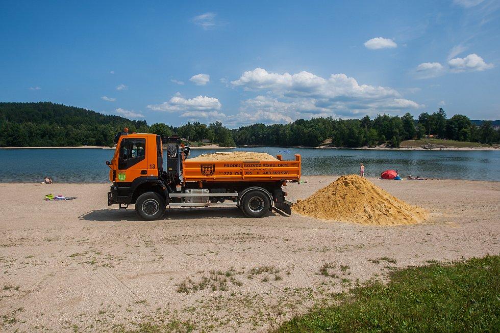 """Pracovníci technických služeb naváželi 16. července 30 tun písku na pláž přehrady v Jablonci nad Nisou. Písek se využije na Pískohrátky, soutěž příměstských táborů ve volné tvorbě dětí na téma """"hrad"""", která proběhne 18. července."""