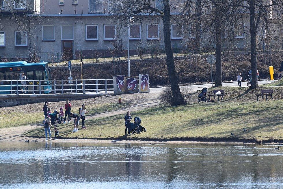 Lidé bez roušek okolo přehrady.