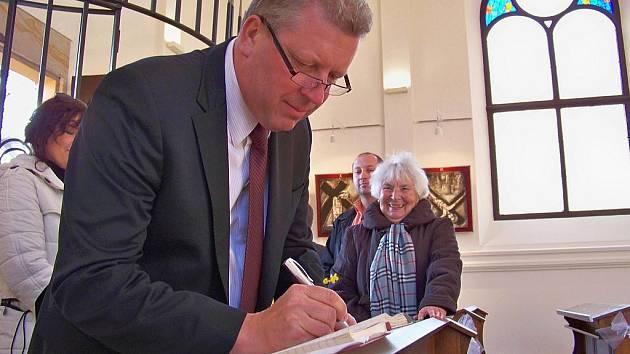 Ministr kultury Jiří Besser se podepisuje do pamětní knihy kaple svatého Vavřince na Malé Skále.