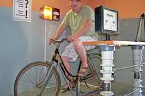 Šlapací kolo. Tomáš Gärtner šlape, za ním na zdi svítí žárovka díky jeho energii.