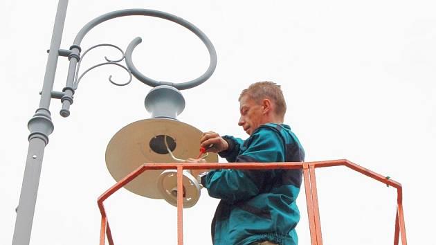 Pracovníci technických služeb umísťují nové lampy na hrázi jablonecké přehrady.