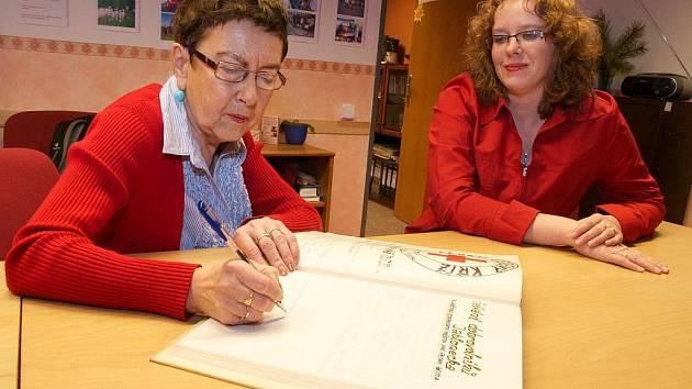 Jiřina Šiklová, známá publicistka a socioložka, se po setkání s dobrovolníky Jablonecka podepsala do kroniky Oblastního spolku Českého červeného kříže, kterou jí předložila jeho ředitelka Kateřina Havlová (vpravo).