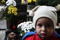 """Již od konce týdne proudí na jablonecký hřbitov davy lidí, kteří chtějí uctít den zesnulých """"dušičky"""". Na snímku malá Terezka Poláčková se svou tetou Petrou."""
