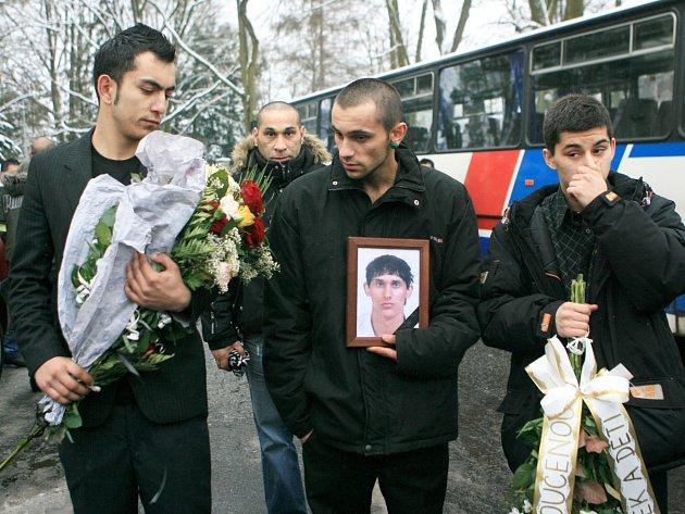 Příbuzní zastřeleného mladíka nesou jeho foptografii při pohřbu, po kterém následoval pokojný pochiod na místo střelby.