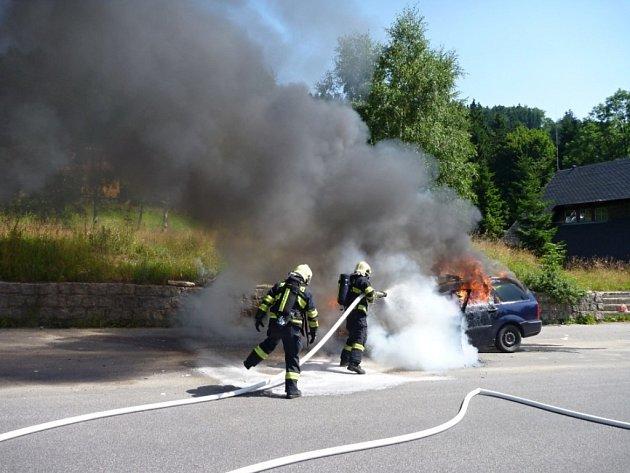Hasiči likvidují požár auta.