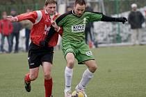 Na umělé trávě ve Mšeně se střel Sokol Maršovice a Sokol Držkov. Na snímku maršovický Jiří Kohoutek ( vpravo v zeleném ) v souboji o míč s držkovským Janem Somrem ( vlevo v červeno černém ).