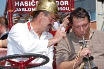 Hasiči Josefu Černému dělal na historickém vozidle velitele vozu Jiří Paroubek. Hasič v dobovém kostýmu právě vysvětluje předsedovi ČSSD foukání na hasičskou trubku. Paroubek nástroj zvládl takřka na první pokus.