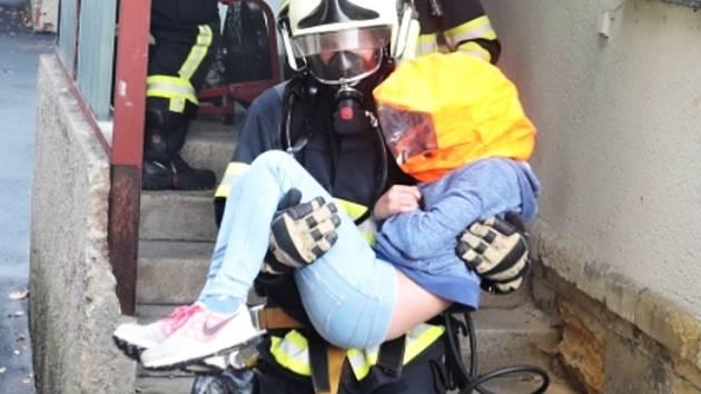 Hasič vynáší dítě z požářiště