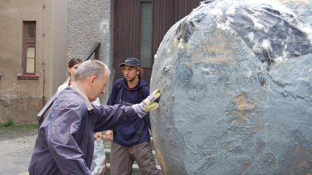 Ředitel Gymnázia Dr. Randy Jiří Kozlovský instaluje maketu balvanu, na kterou studenti nalepí třídní poselství. vyvalení balvanu již patří k tradičním rituálům začátku a konce školního roku.