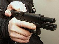 Zbraň v ruce útočníka. Ilustrační snímek.