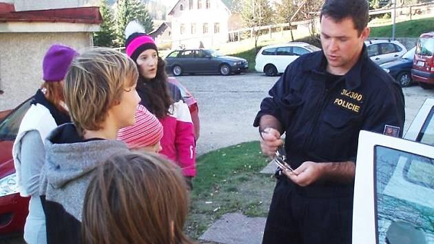 Děti ze střediska ČČK poslouchají výkladu policistů.