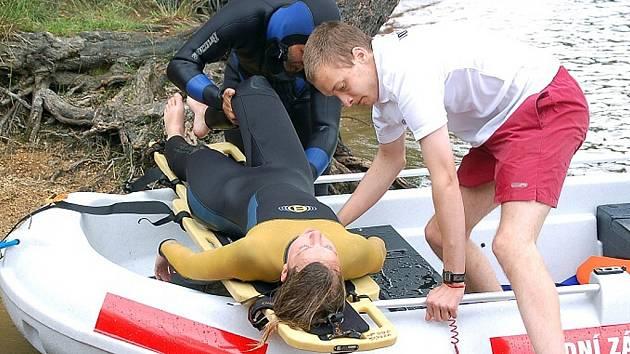 Vodní záchranář Vojtěch Kazda vytahuje figurantku (kolegyni Nikolu Jakoubovou) na člun. Do vody pro ní skočil Petr Šantavý. Nad bezpečností přehrady nyní bdí záchranáři každý den.