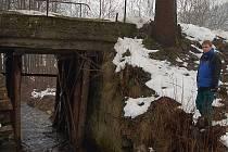 Technický pracovník Obecního úřadu Pěnčín Stanislav Mrázek si prohlíží nejhůře poškozený mostek. Celkově je na Pěnčínsku šest podobných mostků, v lepším technickém stavu.
