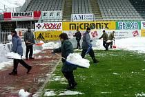 Na trávě fotbalového stadionu na jablonecké Střelnice ležela v neděli souvislá vstva sněhu, kterou pomáhá odstranit 40 věznů ze Stráže nad Nisou.