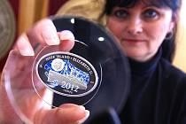 Jablonecká Česká mincovna vyrazila a prodává novozélandskou minci 2012 centů v atypickém tvaru s motivem lodi Titanic. Mince se prodává v hodnotě 2000 korun. Na snímku Jana Bohatá z podnikové prodejny.