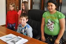 Primátor Šimon (sedící v příslušném křesle) a jeho tři náměstkyně: Denisa, Kristýna a Olga.