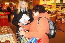 Policistka hovoří v obchodu se starší ženou
