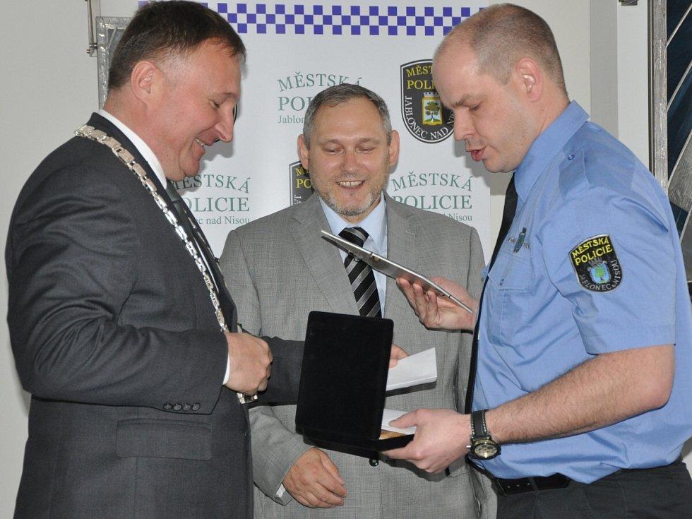 LUKÁŠ JUŘÍK z dopravní a hlídkové služby MP Jablonec, přebírá z rukou primátora Petr Beitla ocenění Strážník roku 2015. Přihlíží ředitel MP Jablonec Luboš Raisner.