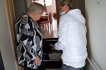 Lucie Kučerová předává obyvatelce domu s byty zvláštního určení objednané zboží.
