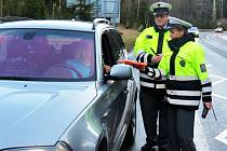 Policisté po kontrole předávají reflexní vestu
