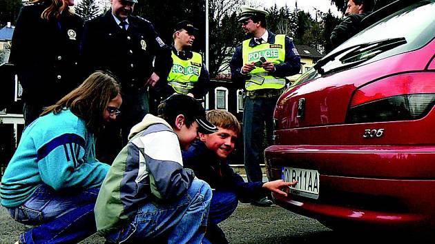 Žáci páté třídy Michaela Riedrová, Filip Rydval a Tomáš Nikl se včera při společné hlídce s policisty ve Smržovce snažili rozluštit platnost technické kontroly i u vozu s polskou poznávací značkou.