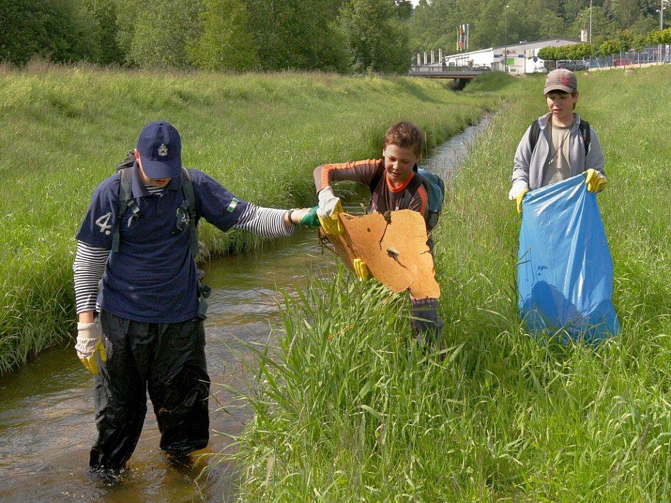 Děti z Junáckého střediska Křišťál v Jablonci nad Nisou čistí koryto jednoho z přítoků Lužické Nisy od odpadků.