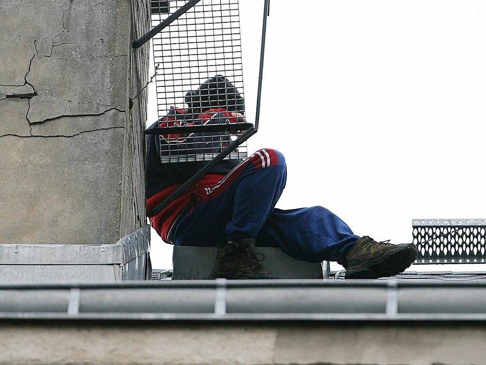 Muž na střeše domu v Pražské ulici v Jablonci chvíli před jedenáctou hodinou dopoledne.