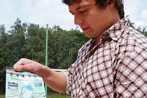 Předseda fotbalového oddílu TJ Sokol Rádlo ukazuje leták, který znázorňuje nové využití fotbalového hřiště