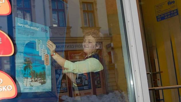 Vedoucí pobočky Irena Sýkorová upravuje výlohu v cestovní kanceláři.