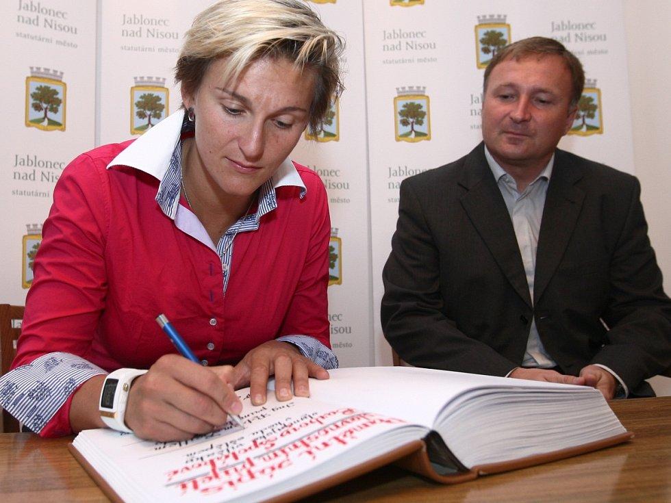 Bára Špotáková se podepisuje do kroniky, přihlíží primátor Petr Beitl