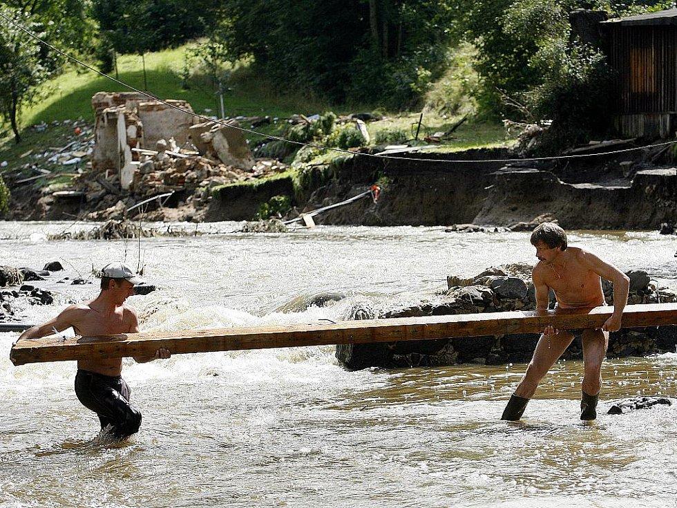 Lidé v zatopených místech potřebují pomoc. Balenou vodu, úklidové prostředky a další nutný materiál. Na snímku pondělní úklid v Heřmanicích.