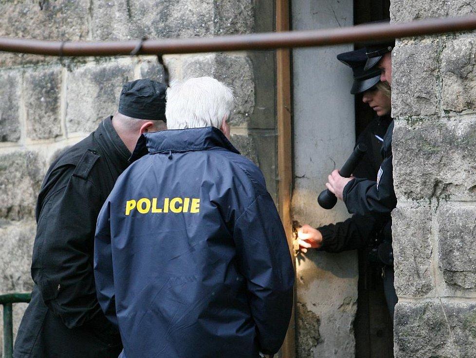 Kriminalisté u dveří, kterými se dostali dovnitř.