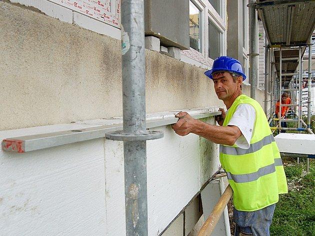 Práce na zateplení budovy. Ilustrační snímek