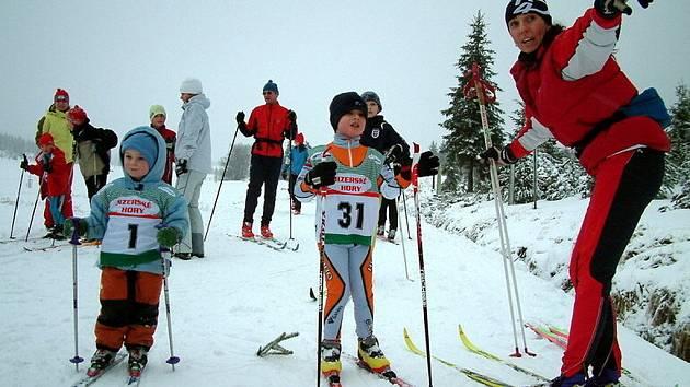 Na Jizerce se konaly první letošní závody v běhu na lyžích. Na snímku Jana Kareisová z Dukly Liberec (č. 1) a Jakub Serra ze Ski klubu Jablonec, kterým ukazuje cestu Michaela Cillerová.