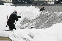 Odstraňování sněhu ze střechy.