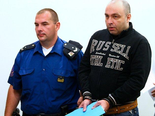 Obžalovaného Petra Ryžáka přivádí justiční stráž do soudní síně.
