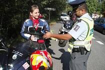 Jablonecký policista kontroluje řidičku motocyklu, která byla zastavena v rámci běžné kontroly na silnici mezi Brodem a Držkovem.