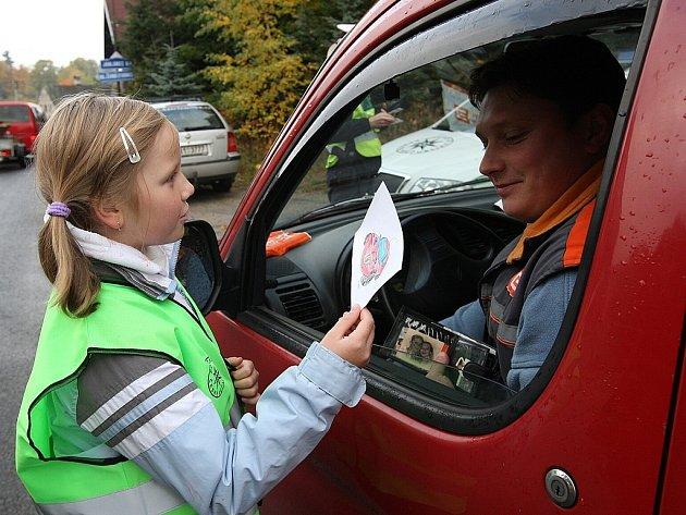V rámci dopravní policejní akce Jezdíme s úsměvem, školáci z Nové Vsi před vlastní školou rozdávali řidičům obrázky. Za dodrženou rychlost smějící se a za překročenou zamračené autíčko.