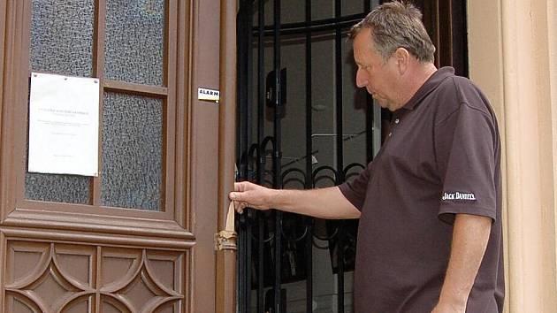 Starosta Malé Skály Jiří Nejedlo kontroluje poškozené vstupní dveře do kaple sv. Vavřince, do které se v noci z úterý na středu pokusil vloupat neznámý pachatel.