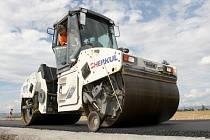 Dokončení silnice stavebními stroji. Ilustrační snímek.