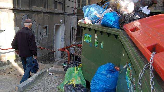 Přeplněné popelnice musí míjet občané cestou na autobusové nádraží.