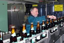 Etiketovací stroj jede naplno, Lubomír Šojda kontroluje správné usazení etiket a doplňuje zásobníky