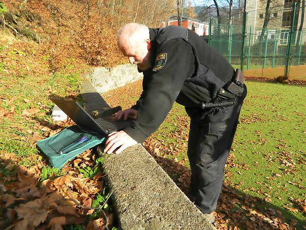 Strážník instaluje fotopast - ilustrační foto.